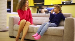 Woman in red dress and girl talk sitting on sofa at apartment. Stock Footage