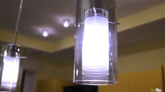 Three cylindrical shaped lamp hanging from ceiling in kitchen. Stock Footage