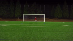 The camera follows a soccer player down the field as he makes a goal - stock footage
