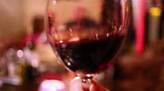 Hand shakes dark red wine in a transparent wineglass. Stock Footage