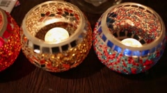 Three bowls made of coloured glass with burning candles inside. Stock Footage