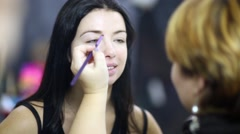 Stock Video Footage of Makeup artist paints eyebrow of girl model using brush.
