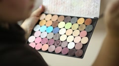 Stock Video Footage of Visagiste takes with brush one of tones from eyeshadow collection
