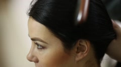 Stock Video Footage of Visagiste hands comb hair of dark-haired young girl model.