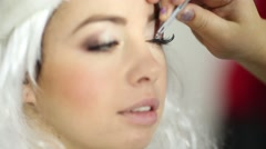 Makeup artist fixes with forceps false eyelashes on upper eyelid Stock Footage