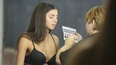 Visagiste applies makeup on eyelids of model in bra using brush. - stock footage