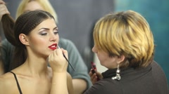 One visagiste makes hairdo and other paints lips to girl model. - stock footage