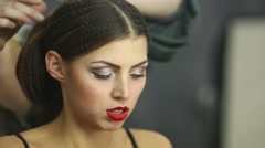 Visagiste makes hairdress to girl model in studio. - stock footage
