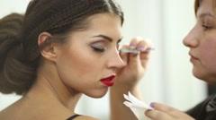 Stock Video Footage of Makeup artist glues false eyelashes using forceps to eyelids of model