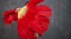Young girl dancer with fan poses against grey background. Stock Footage