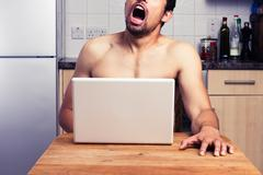 Young naked man watching porn in his kitchen - stock photo