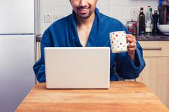 Man in robe checking emails and having coffee - stock photo