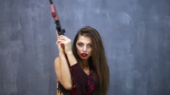 Model dances with toy assault rifle against blue-grey background. Stock Footage