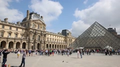 Tourists in Court of Napoleon with glass pyramid in Louvre museum. Stock Footage