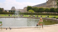 People get rest around fountain in Garden of Tuileries Stock Footage