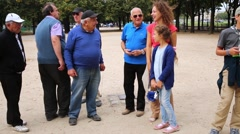 A group of men playing petanque talk with woman with children. Stock Footage