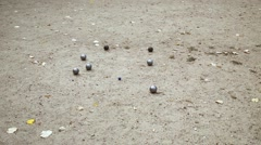 Blue cochonnet and several petanque balls on sandy ground. Stock Footage