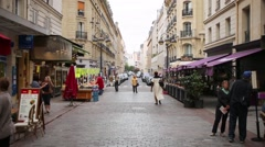 People walk by a narrow pedestrian street with granite paving. Stock Footage