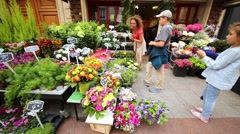 Mother and children look at flowers in flower shop on street. Stock Footage