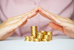 Protect new business start-up  - with hands and coin - stock photo