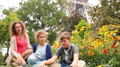 Smiling mother, boy and girl sit on grass near flower garden Stock Footage