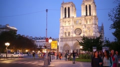 People walk on square against Notre Dame Cathedral in evening. Stock Footage