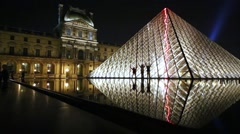 Three human silhouettes against illuminated glass Louvre Pyramid Stock Footage