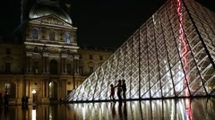 Three human silhouettes walk one by one against Louvre Pyramid Stock Footage
