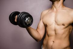 Fit young bodybuilder training with dumbbell Stock Photos
