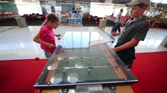 Children play soccer game machine in waiting room of Airport. Stock Footage