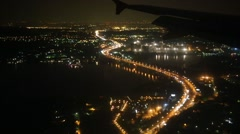 Illuminated settlements and roads through porthole of flying airplane Stock Footage