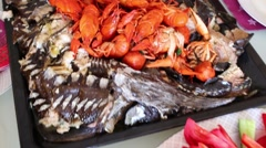 Tray with boiled crawfishes and sturgeons baked in oven then cut Stock Footage