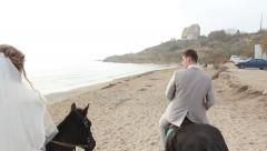 Bride and groom walking along the beach on horseback Stock Footage