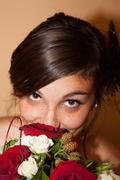 Portrait of an happy and pretty woman with bouquet of red and white flowers Stock Photos