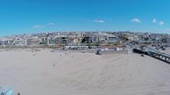 People walk by Manhattan Beach Pier along sandy beach Stock Footage