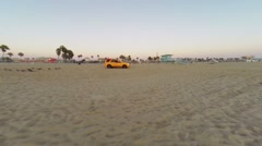 Yellow car rides by Venice Beach at autumn evening during sunset. Stock Footage