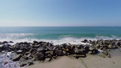 Pile of stones lay on shore of pacific ocean near Venice Beach Stock Footage