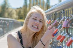 Beautiful young blond woman holding padlocks - stock photo