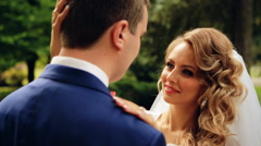 Bride and groom in love looking at each other at beautiful green park shot in Stock Footage