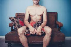 Young naked man on sofa with disturbed look on his face Stock Photos