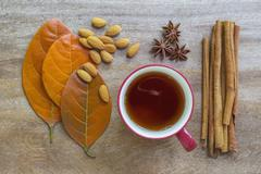 Still life of autumn leaves, almond seeds, cup of tea, anise cloves, and - stock photo