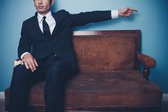 Businessman on sofa pointing right Stock Photos