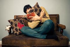 Young man is scared and hiding his face behind a cushion - stock photo