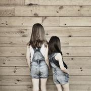 Rear view of two girls wearing dungarees standing side by side against hardwood Stock Photos