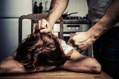 Man physically abusing his wife Stock Photos