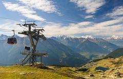 Switzerland, Bettmergrat, Overhead cable car passing by tower in Kuvituskuvat