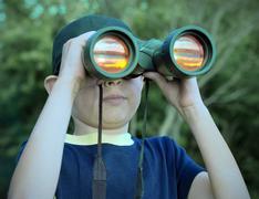 Boy looking through binoculars - stock photo