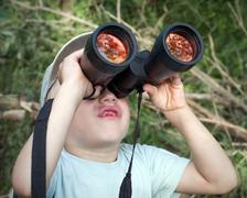 The little boy looks up at binoculars - stock photo