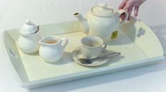Pour tea into a cup on a tray Stock Footage