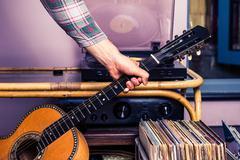 Hand picking up guitar next to box of vinyl Kuvituskuvat